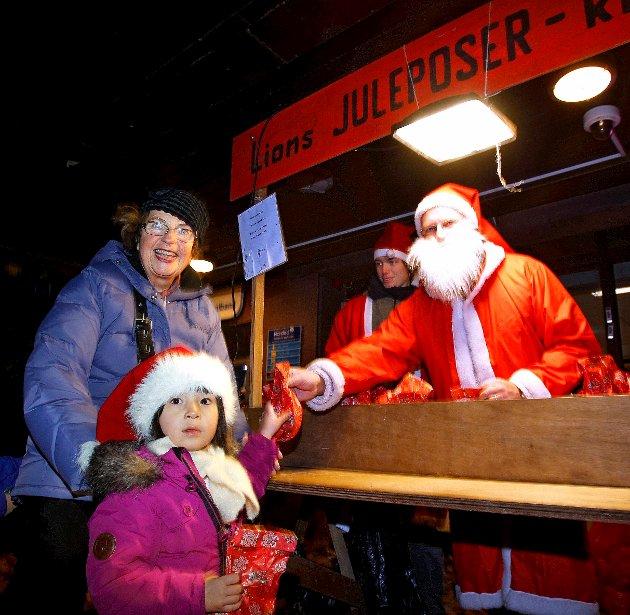 2013: Julegateåpning og tenning av julegrana foran Moss kirke. Sigrid Urdal med bestemor Solveig Haug Urdal får pose av Kai Roger Hennum i Lions.