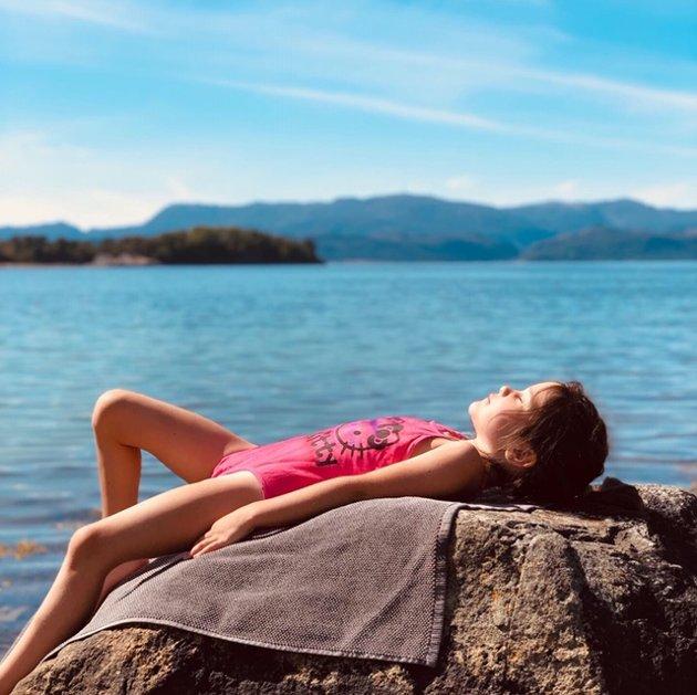Michaela Jørgensen (6) har fått den rosa Hello Kitty-badedrakta på, og solar seg i Borvika.