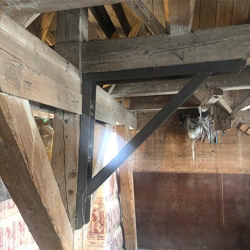 SKJEVT: Bygget er så skjevt innvendig at trebjelkene må stives opp med vinkler av stål. I tillegg er det stivet opp med stålvaiere som går gjennom hele bygget på tre forskjellige steder.