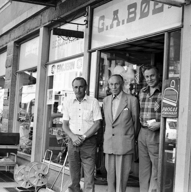 90 år i 1977: To generasjoner i firma G.A. Bøe utenfor  i Storgaten 13. Frithjof Bøe senior flankeres av sønnene Frithjof Bøe jr. (til venstre) og Kaare Bøe.