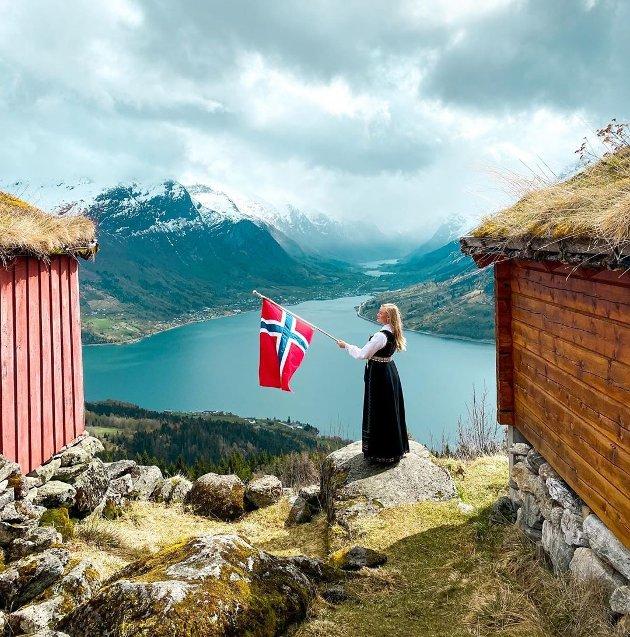 HURRA: Katrine Bruland viftar det norske flagget med vakker norsk natur i bakgrunnen.