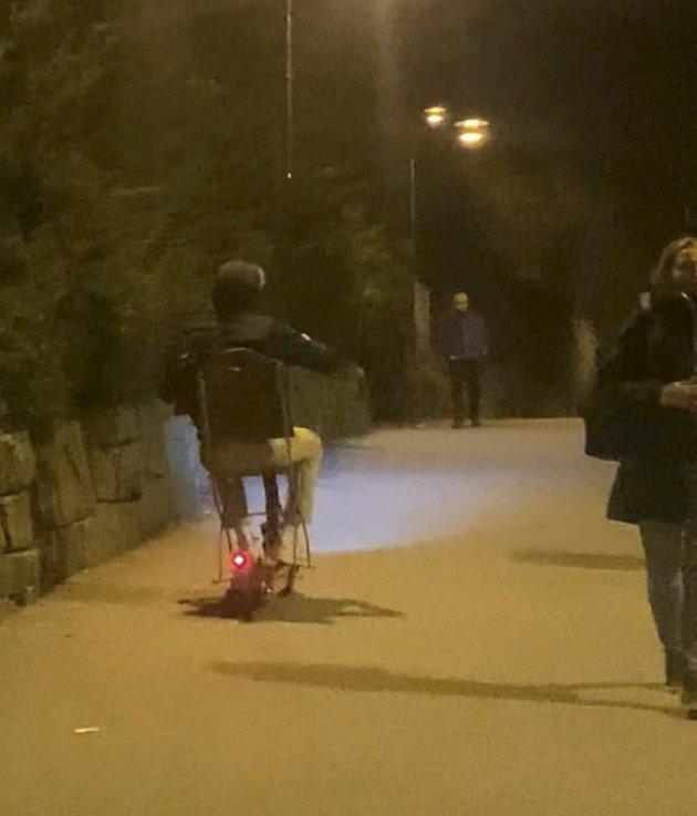 Denne karen kjører el-løperhjul gjennom sentrum sen nattetid sittende på en klappstol.