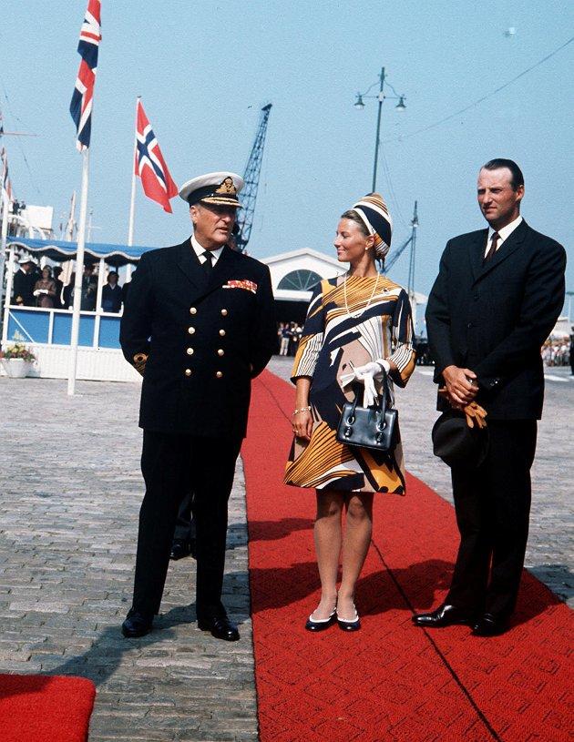 "Dronning Elizabeth i Norge sammen med familien. Dronning Elizabeth ankommer til Bergen med ""Britannia"" 7. august 1969. Kong Olav, kronprinsesse Sonja og kronprins Harald ønsker dronningen velkommen til Bergen."