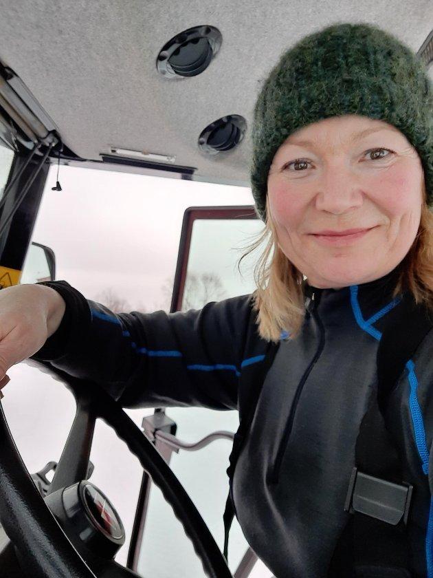 Cecilie Hansen på traktoren på gården sin i Pasvik