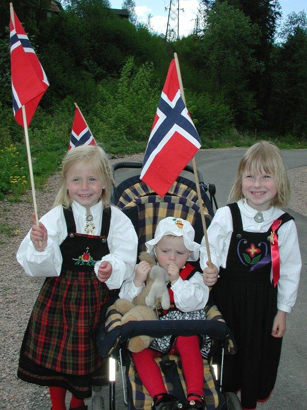 Thea L. Thue (4), Ingrid Tryti (2) og Anna Emilie Tryti (4) feiret 17. mai på Sydskogen skole. Minstejenta hadde med seg kosedyret i tilfelle hun trengte å dele inntrykkene med noen. Fra 2002.