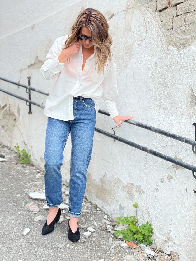 Linn Jeanette Wissestad i en trendmiks av stor skjorte, jeans, hæler og bikinitopp.