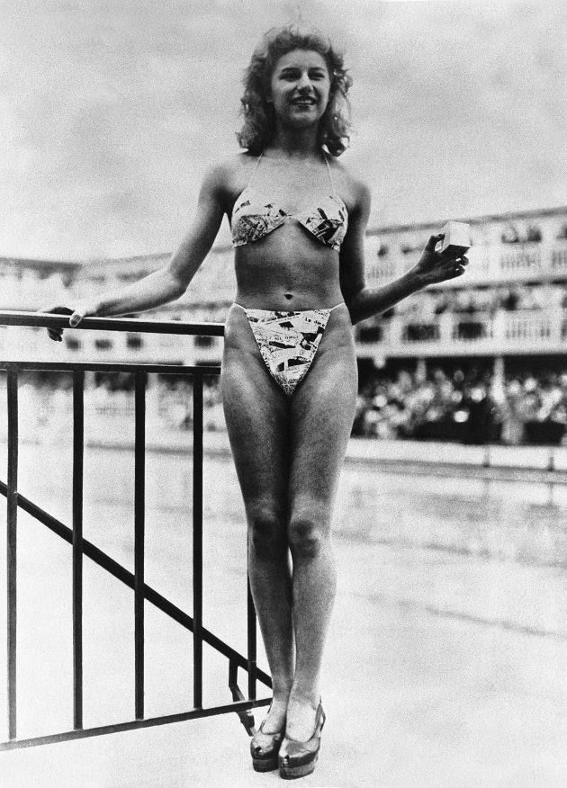 Da bikinien skulle lanseres var det så kontroversielt at det var vanskelig å få vanlige fotomodeller til å stille opp. Løsningen var at designer Louis Réard hyret inn Micheline Bernardini. Han introduserte bikinien på det store offentlige badet Piscine Molitor den 5.juli 1946 med det som var en 18 år gammel nakendanser fra Casino de Paris. Bikinien slo ned som en bombe, og Le Figaro i Frankrike hyllet lanseringen som en stor frigjøring av kvinnen og livets herligheter.  Boksen hun holder er en fyrstikkboks som er ment for å vise hvor liten plass bikinien tar om den pakkes sammen.