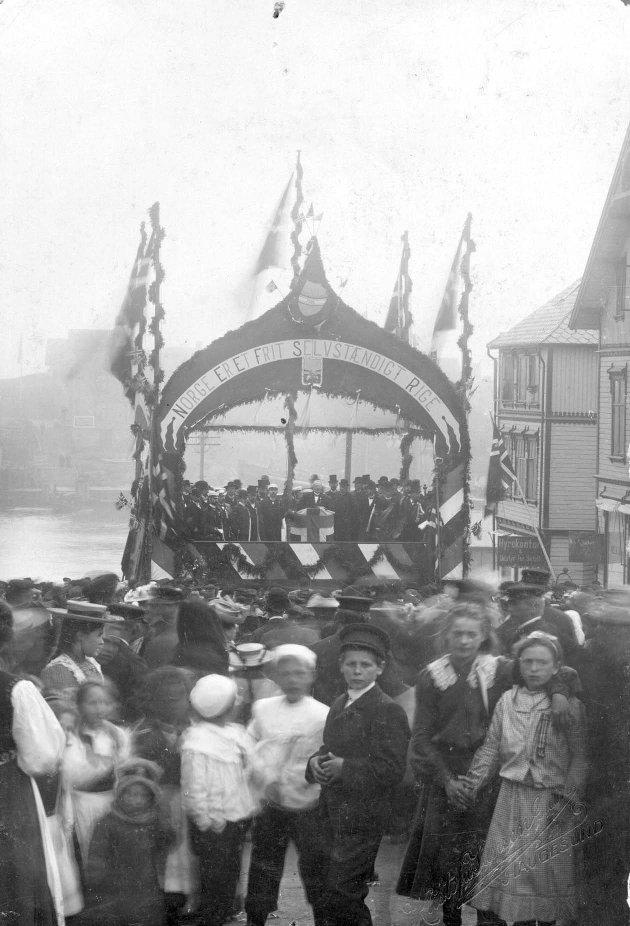 1905: Kristofa Jansen Grøn var en av svært mange fotografer som foreviget høytidelighetene i 1905. Her er barn og voksne samlet i Torgbakken 17. mai 1905. Tribunen er pyntet og dekorert med norske flagg og ordene «Norge er et frit, sælvstendig rige».