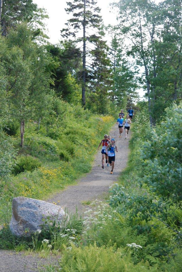 Her kommer de første løperne i full fart opp ved Strandelva.