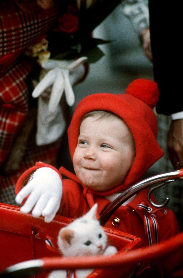 Asker 19730517: prinsesse Märtha Louise (1 år 8 mndr) fotografert på Skaugum i forbindelse med nasjonaldagen 1973. Bildet: prinsessen klapper en kattunge. Rød kåpe og lue .  NTB arkivfoto: Erik Thorberg / NTB