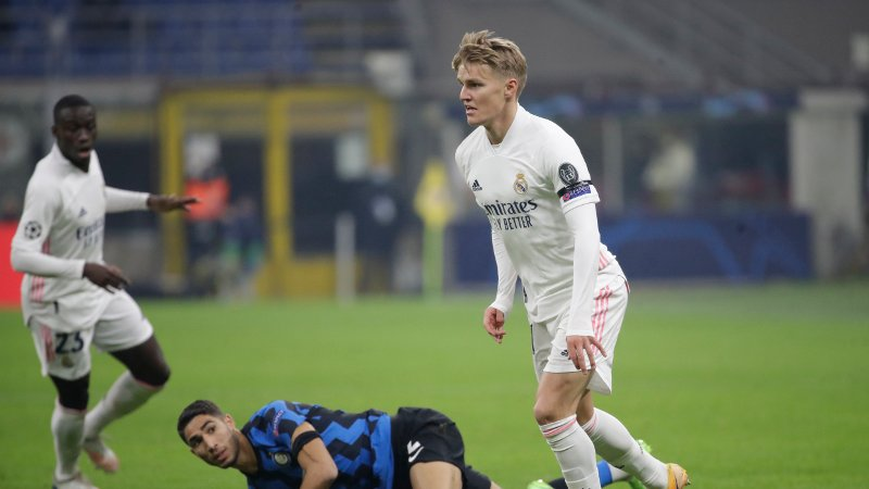 Real Madrid's Martin Odegaard, right, and Inter Milan's Achraf Hakimi vie for the ball during their Group B, Champions League soccer match between Inter Milan and Real Madrid at the San Siro Stadium, in Milan, Italy, Wednesday, Nov. 25, 2020. (AP Photo/Luca Bruno)