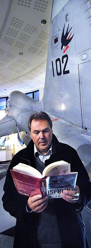 """Den kalde krigen. Asbjørn Jaklin leser i sin nye bok """"Isfront"""" flankert av en F5. En av mange jagere som var sentrale i den kalde krigen ? og som pryder omslaget. Begge foto: Hans Trygve Holm"""
