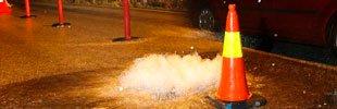 Vannet fosser opp gjennom et bekkalokk i Øvre Fyllingsvei på Melkeplassen.