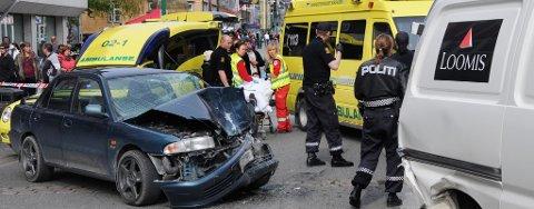 ÅSTEDET: En kvinne i 50-årene døde av skadene hun ble påført da en bil kjørte gjennom Storgata og traff henne i stor fart. Her fraktes sjåføren av ulykkesbilen bort av ambulansepersonell.