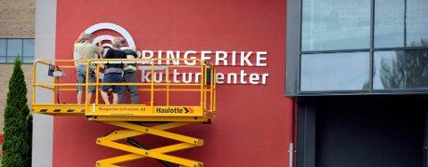De nye skiltene til Ringerike kultursenter henges opp på veggen.