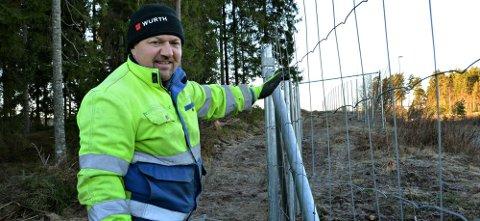 GJERDEMONTERING: Pavel Goszcz i ferd med å montere gjerdet på sørsiden av Lundebykrysset.