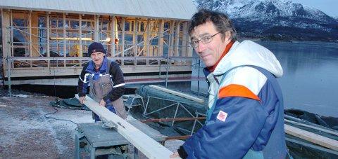 Bygningsarbeiderne Arvid Larsen og Kjell Olsen er i full sving med å reise naustet med leilighet i hovedplan og hems.