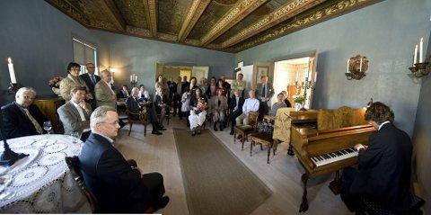 Imponerende rom: Barokkstua er blitt et fantastisk rom med den originale dekoren i taket. Her er gjestene samlet i den imponerende stua ved åpningen i går, mens Marius Astrup Thoresen spiller Grieg-stykker på Archer-familien gamle flygel. (Foto: Erik Berge)