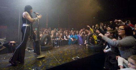 """Wig Wam markerte fredagens plateslipp med konsert i Brygga Kultursal i Halden lørdag kveld. Her demonstrerer vokalist Åge Sten """"Glam"""" Nilsen god kontakt med publikum. (Foto: Tobias Nordli)"""