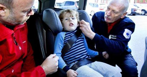 VIKTIG SIKRING: Trafikksikkerhetsforskerne Kim Ankersten (t.v.) fra Eidsvoll og Trond Boye Hansen fra Nittedal jobber med prosjektet «Barn i bil». Her demonstrerer de riktig sikring.Foto: Tom Gustavsen