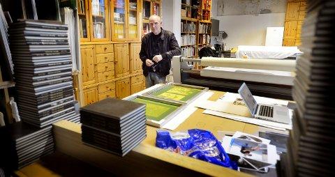 Karl O. Orud er en erfaren kunstner. Her står han ved et bord i sitt verksted i Spinneriet, hvor det ligger snart utstillingsklare silketrykk.