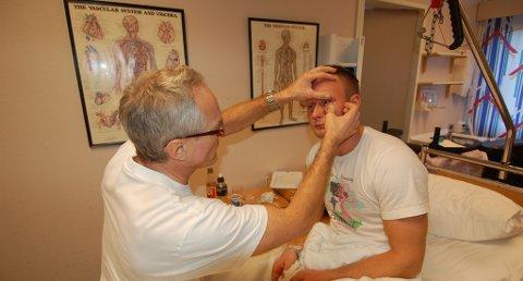 Øyelege Frode Halvorsen fra Risør behandler Thomas Ertsås etter rakettskaedene han fikk nyttårsaften. Han legger ikke skjul på at Thomas har hatt kjempeflaks. FOTO: Svein Walstad