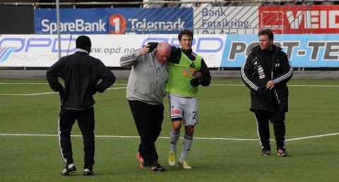 UFLAKS: Dag Alexander Olsen skadet seg på Odd-trening 5. november. Nå vil han trene seg opp igjen i skiensklubben, men får nei fra trener Dag-Eilev Fagermo. Her hjelpes angrepsspilleren av banen av Morten Rønningen. Til høyre: Bård Homstøl.