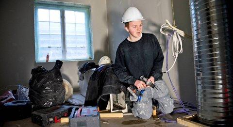 Lærling Ole Petter Hellesø Milde skal hjelpe å dekke til en ventilasjonsboks i det gamle bygget.