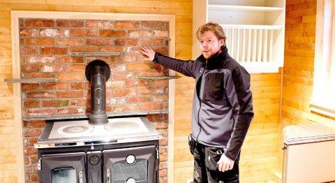 KJØKKEN: En vedovn som varmer opp den vannbårne varmen i huset er plassert på kjøkkenveggen inn mot stuen. Ovnen forvarmer også vannet til varmtvannsberederen. Sammen med solfangere på taket, kommer husets oppvarming hovedsakelig fra denne vedovnen. Teglsteinen bak er fra pipen til hytten som tidligere sto på tomten. ?Jeg regner med å bruke lite strøm til oppvarming av huset, sier Ruben Oddekalv.