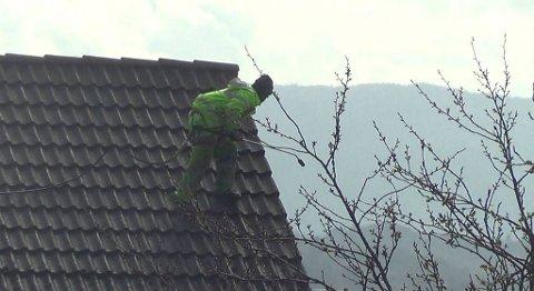 Her jobber mannen usikret på hustaket. Like etter grep Arbeidstilsynet og politiet inn, og stanset arbeidet.