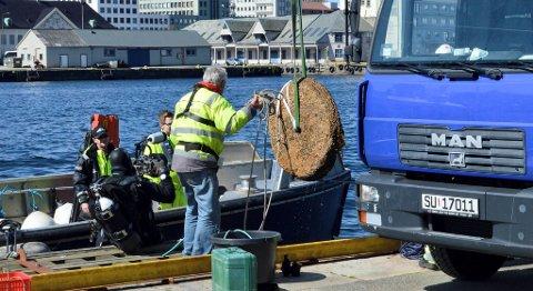 Kvernsteinen som her henger i en stropp er nettopp kommet til overflaten etter å ha ligget på bunnen i rundt 300 år. T.v. Arild Marøy Hansen fra Sjøfartsmuseet.