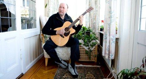 Ole Thomsen (61) øver med gitaren hjemme i vinterhagen i leiligheten i Jørgen Moes gate.