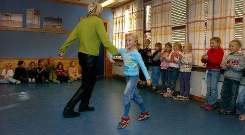RUNDT OG RUNDT: Marianne Kostøl tar med seg elev Martine Evenrud Solbakken i en svingom på Korta skole, mens de øvrige elevene synger og klapper.FOTO: HENNING GULBRANDSEN