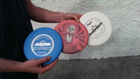Diskene som brukes i frisbeegolf: Blå putter, rød driver og hvit midrange.