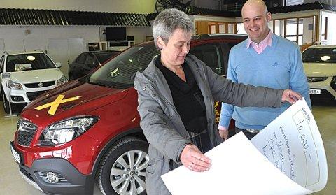 VANT: Rakkestad-damen Marit Røste har fått det synlige beviset på at hun og mannen har vunnet en London-tur til 10.000 kroner. Simen Bystrøm hos Auto Askim er blid gevinstutdeler.