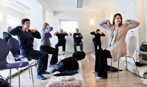 Styrke og avspenning. ? Håndflatene opp mot skuldrene, tomlene bak og de andre fingrene fram, sier Veetamo Kari Lyngmo (t.h.) og leder øvelsene i medisinsk yoga for Anne Nygård (t.v.) og andre med Parkinson samt noen pårørende. Nå er de med i et forskningsprosjekt for å finne ut om medisinsk yoga har noen virkning for dem med Parkinsons sykdom.Alle foto: Hans Trygve Holm