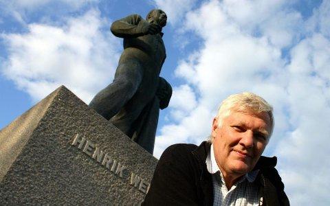 MANGE STATUER: Lederen i Eidsvoll historielag viser vei til Eidsvolls mange statuer. Her er han foran statuen av Henrik Wergeland. Den står ved Eidsvollsbygningen. ALLE FOTO: ELISABETH BRINCH SAND