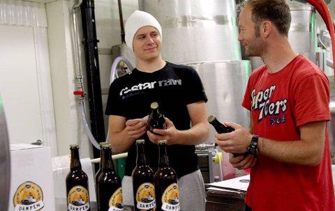 DAMPØL: Kristoffer Møgster Berge og Espen Lothe er i full gong med å klistre etikettar på flaskene til Fjordsteam-ølet. Kinn Bryggjeri har for høvet brygga dampøl etter gamle oppskrifter frå San Francisco. Foto: Iris Kvellestad