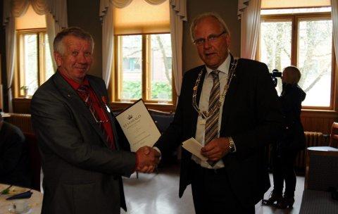 Ordfører Øystein Beyer festet medaljen på jakka til Tittei Fosse.