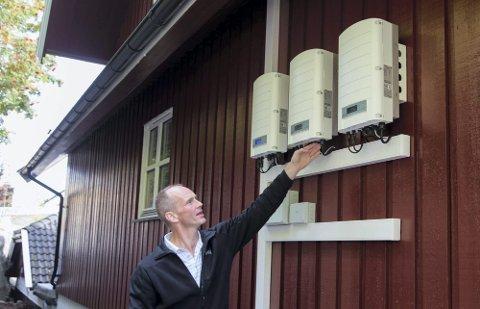EN DEL AV ANLEGGET: Panelene på husets bakvegg inneholder blant annet vekselrettere. De omformer likespenning fra solcellepanelene til vekselspenning som går inn i sikringsskapet, forklarer Thor Christian Tuv.