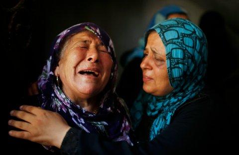 Palestinerne sørger over sine døde. Bildet er tatt mens medlemmer av Hamad-familien blir gravlagt i byen Beit Hanoun nord på Gazastripen. Israel varslet søndag nye angrep mot den nordlige delen av Gazastripen.