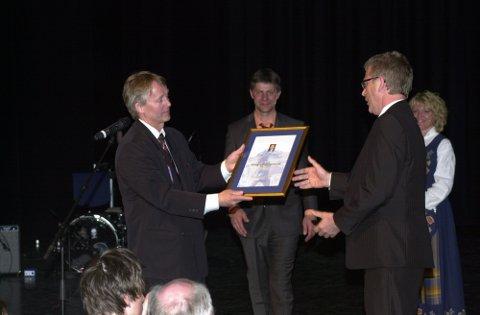 Prisutdeler Thorvardur Gunnlaugsson i Svolvær Innbyggerforening deler ut prisen Årets Svolværing til Hugo Bjørnstad i Lofoten Kulturhus mens konferansierne Bjørn Nilsen og Ingunn Rottem Nilsen applauderer.