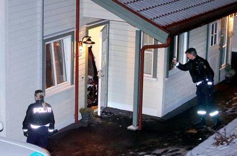 JAKT PÅ TYVER: To polititjenestemenn fra Telemark politidistrikt undersøker skadene på inngangspartiet av leiligheten i Porsgrunn der tre fremmede personer banet seg vei søndag kveld.