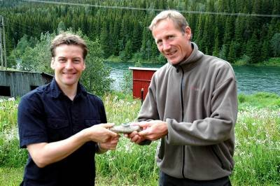 Allan Berg fant den 4-5000 år gamle steinøksa på den andre siden av elva i bakgrunnen. Museumsleder Tormod Steen (t. h.) betegner funnet som sensasjonelt. Foto: Klaus Solbakken