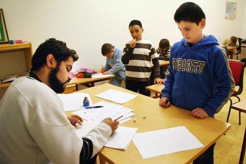 Etter at elevene har skrevet de arabiske setningene i boka, er det opp til lærer Omami Amin for sjekk. Her er det Mansor Aldamor som sjekkes, mens Sofian Orbiy ser på.
