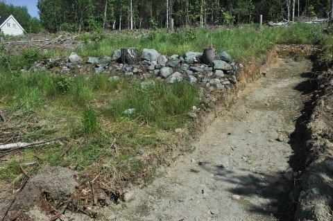 TERRASSE: Terrassen av stein er bygget opp for å holde jorda på plass. Gjennom terrassen går en av arkeologenes prøvesjakter.