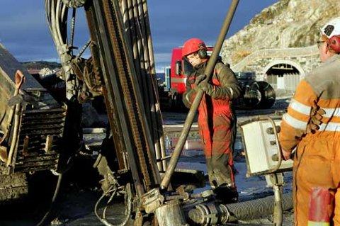 BORER I HØSTSOLA: Terje Verkland setter på plass nye borerør for å komme langt nok ned i bakken til å varme opp det nye velferdsbygget til StatoilHydro.