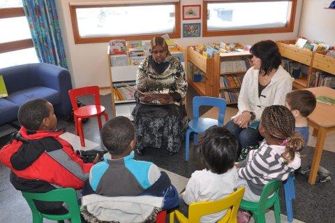 Eventyr på andre språk: Disse barna fikk høre eventyret «Bukkene bruse» på somalisk. Det er Barwago Ibrahim Ali (t.v.) som leser. Mevlyde Krasniqi leste senere det samme eventyret på albansk. (foto: Bjørn Jakobsen)