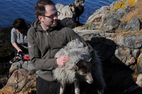 Her er en som blir med i båten. Asbjørn Ole Karsteinsen holder fast tak i ungsauen.