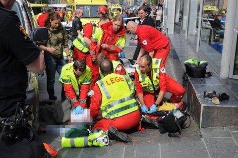 MISTET LIVET: Her forsøker ambulansepersonell å få liv i kvinnen i 50-årene som døde etter å ha blitt påkjørt midt i Storgata onsdag ettermiddag.